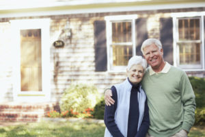 Senior couple in front of their home