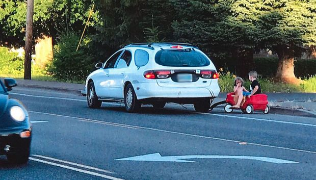 Woman Pulls Tows Kids Behind Car During Rush Hour