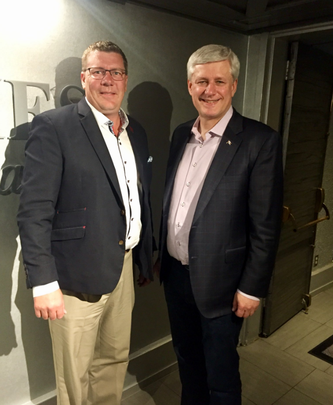No conflict found after Premier Moe & former PM Harper seen at Rider game
