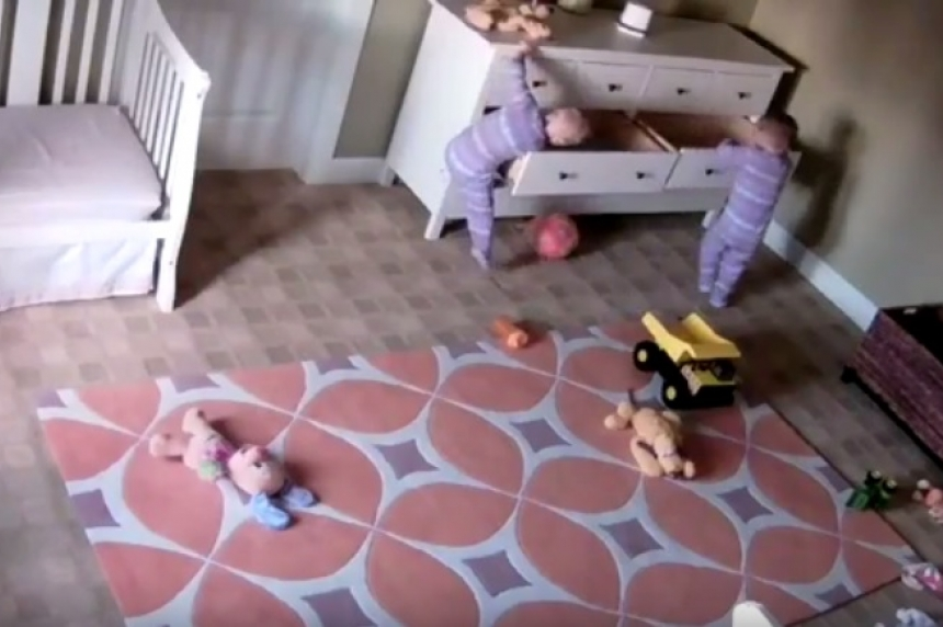 Toddler boy pushes fallen dresser off twin brother in video