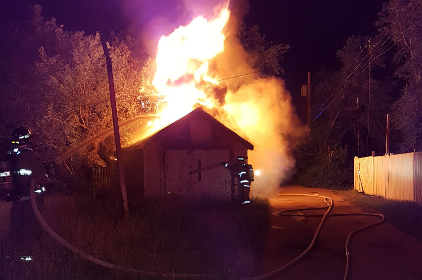 Early morning fire destroys garage, downs power line on Ave S