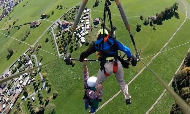WATCH: Tandem hang gliding passenger hangs on after pilot forgets to attach him...