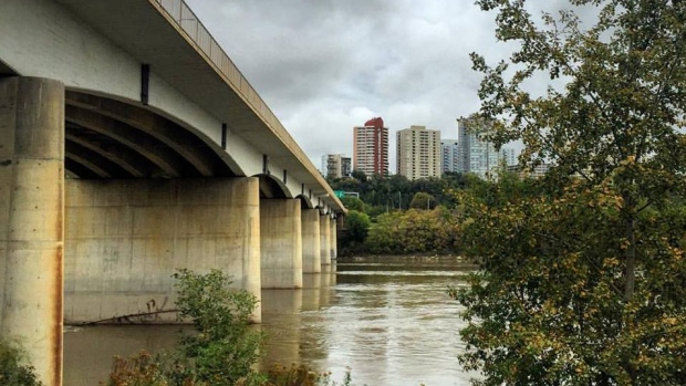WOMAN CLINGS TO BRIDGE POST WHEN SHE'S SWEPT AWAY BY THE NORTH SASK